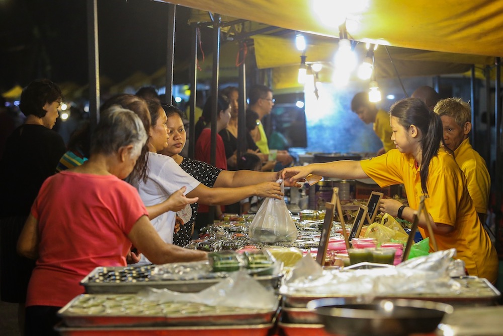 You can distinguish the hawkers at this 'pasar malam' by the yellow T-shirts they wear... the stalls also have standard canopies. — Picture by Hari Anggara