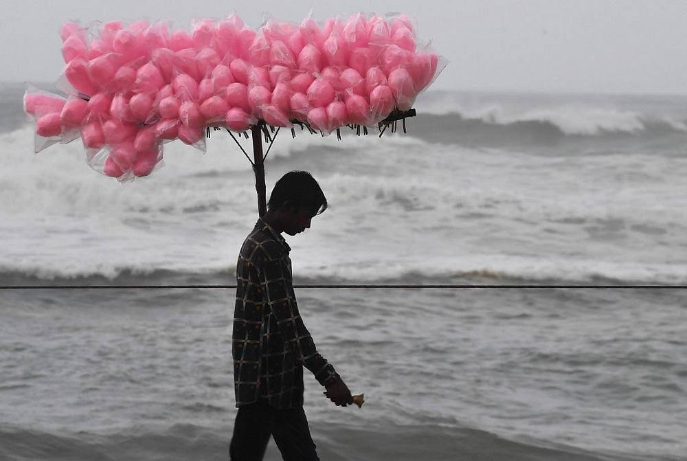 An Indian candy vendor walks along a closed beach in Puri in the eastern Indian state of Odisha on May 2, 2019 as cyclone Fani approaches the Indian coastline. — AFP pic