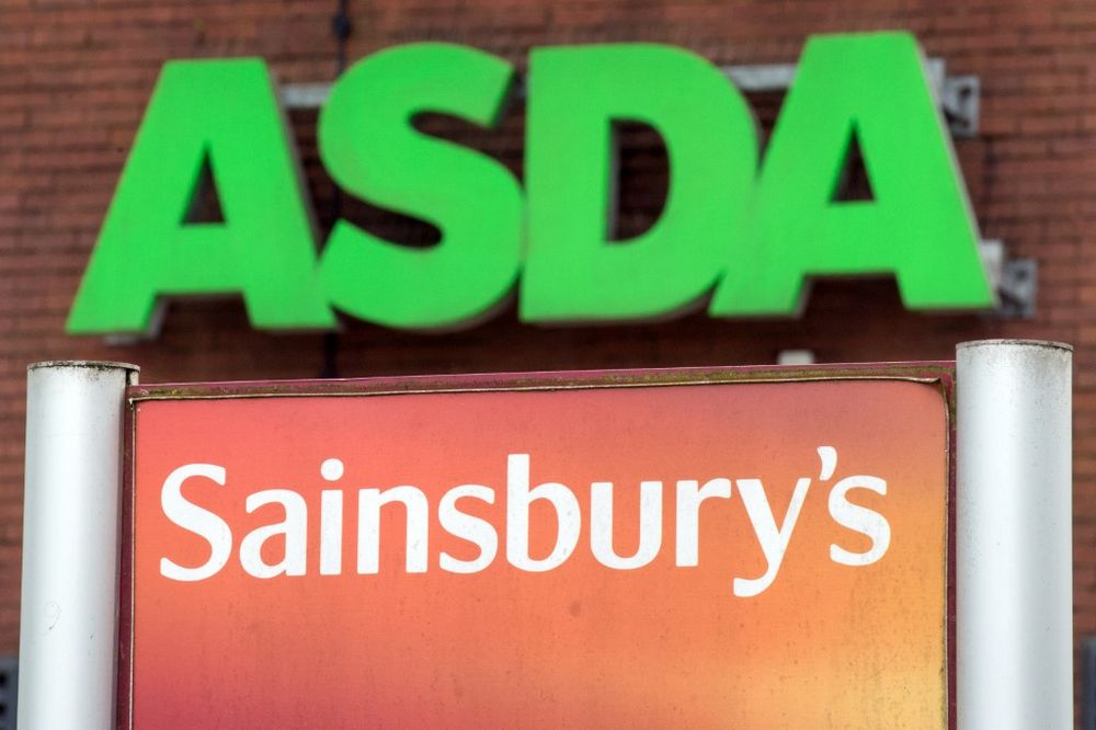 Logos of supermarket chains Asda (top) and Sainsbury's are pictured outside adjacent branches of their stores in Stockport, England, April 30, 2018. — AFP pic