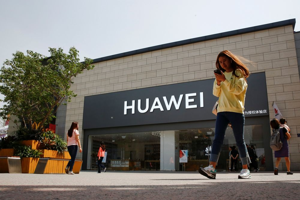 A woman looks at her phone as she walks past a Huawei shop in Beijing, China May 16, 2019. — Reuters pic