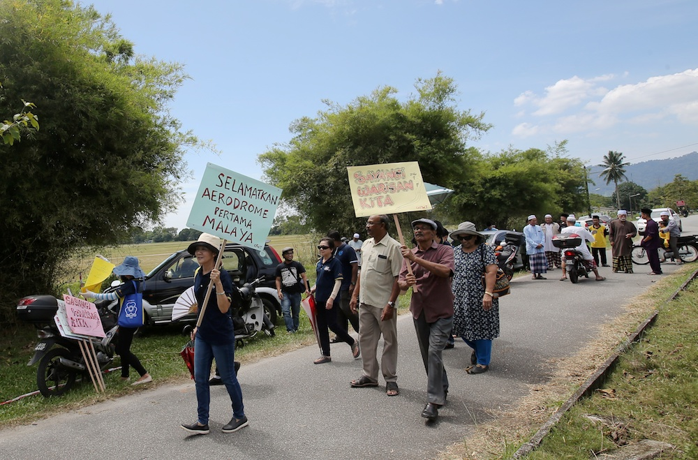 People hold banners during a demonstration against the rumoured sale of Aerodome Taiping in Taiping June 14, 2019. — Picture by Farhan Najib
