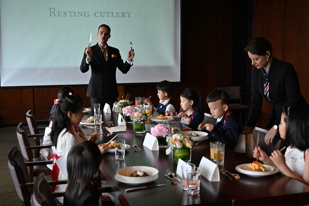 This picture taken on June 1, 2019, shows Guillaume de Bernadac teaching children how to use cutlery during an etiquette and manners class in central Shanghai. ― AFP pic
