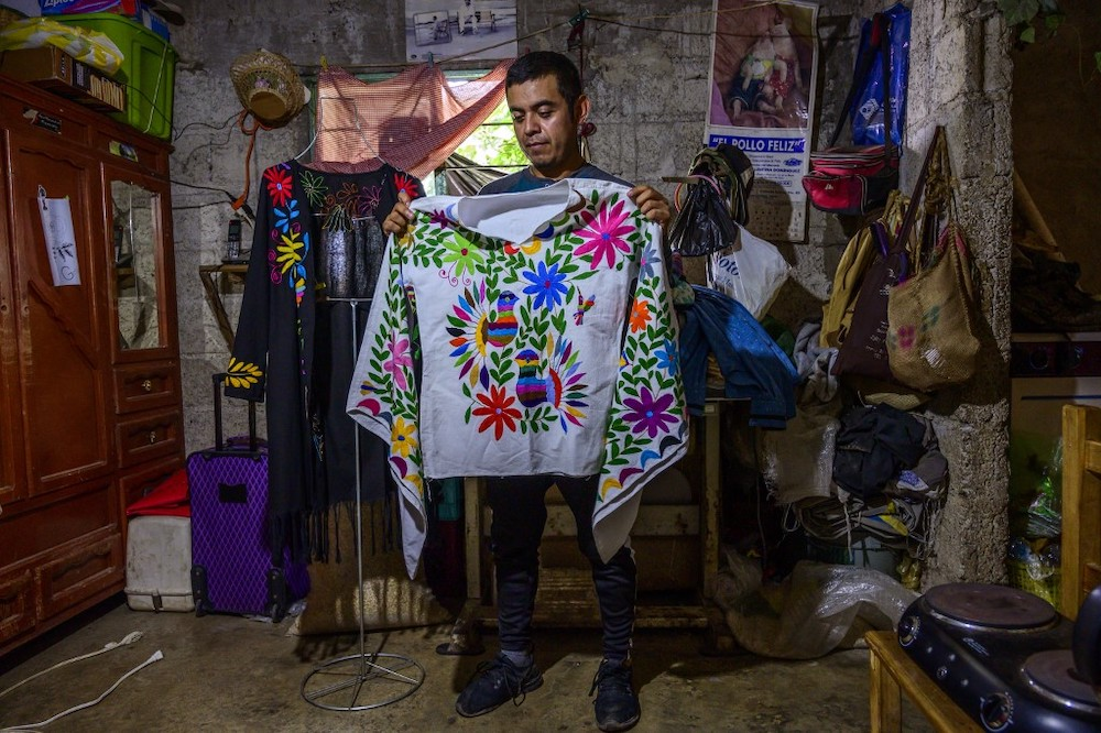 Mexican artisan of the Otomi ethnic group Oliver Teodoro Lopez, shows one of his designs at his workshop in San Nicolas Village, in Tenango de Doria, Hidalgo state, Mexico, on June 18, 2019. — AFP pic