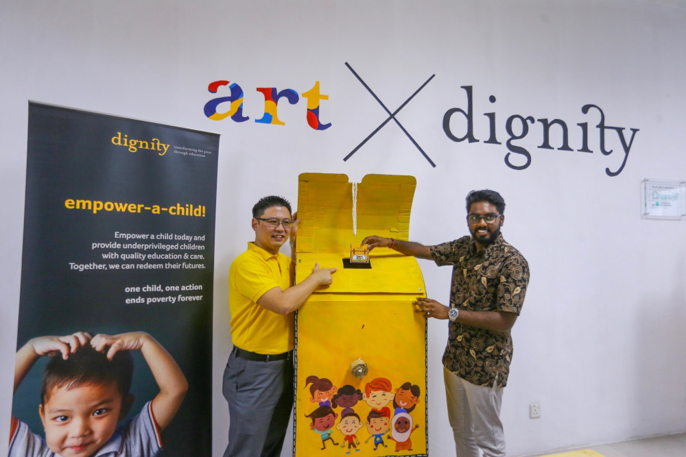 (From left) Dignity for Children Foundation chairman, James Ling with Batu MP P. Prabakaran as they make the first donation for the 'Dignity Schoolbag' initiative. — Picture by Hari Anggara