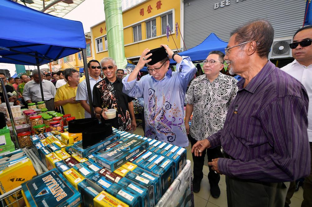Chief Minister Datuk Patinggi Abang Johari Openg tries on a songkok while officiating the Gawai Raya Street Bazaar in Kuching May 25, 2019. — Bernama pic