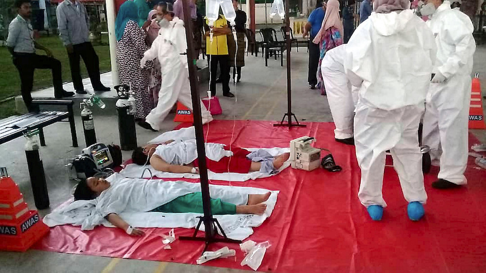 Emergency services staff attend to students with reported breathing difficulties at Sekolah Agama Taman Mawar in Pasir Gudang June 20, 2019. — Bernama pic