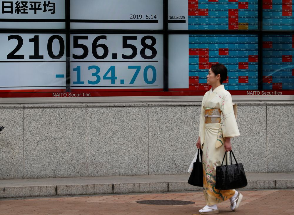 A woman wearing a kimono walks past an electronic board showing the Nikkei stock index outside a brokerage in Tokyo May 14, 2019. — Reuters pic