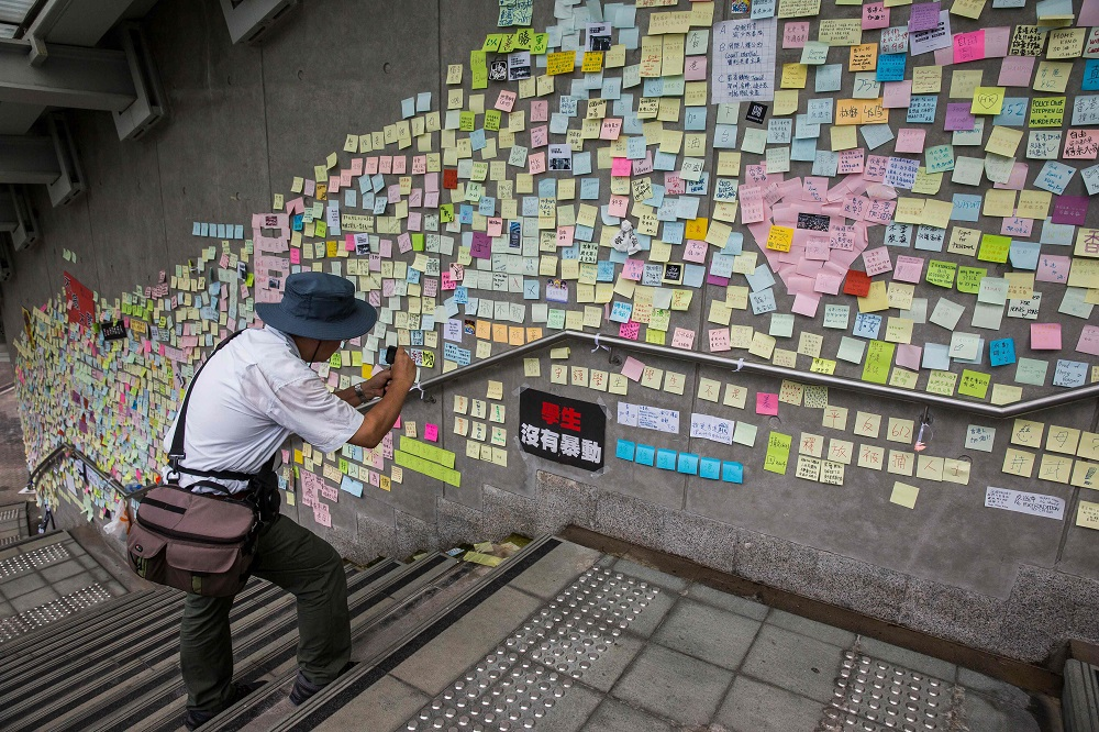 This picture taken on June 22, 2019 shows a man taking photographs of artwork and messages in support of protesters opposed to a China extradition law posted on the 'Lennon Wall' outside the government headquarters in Hong Kong. ― AFP pic
