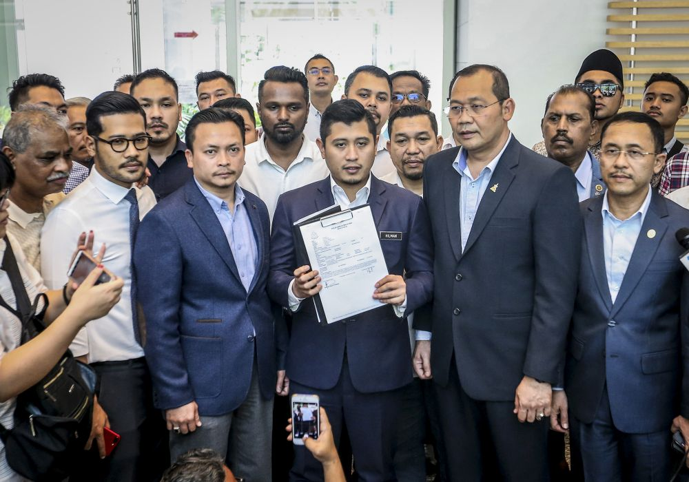 Datuk Seri Azmin Ali's political secretary Muhammad Hilman Idham holds up a copy of the police report at the Federal Territories Islamic Religious Department in Putrajaya June 13,2019. — Picture by Firdaus Latif