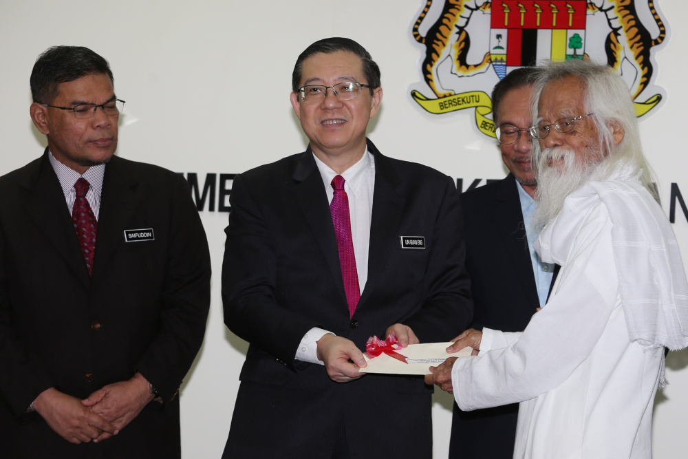 Finance Minister Lim Guan Eng presenting the monthly living allowance to national laureate Datuk Seri A. Samad Said at the Finance Ministry June 24, 2019. With him are PKR president Datuk Seri Anwar Ibrahim and Domestic Trade and Consumer Affairs Minister Datuk Seri Saifuddin Nasution Ismail. — Picture by Choo Choy May