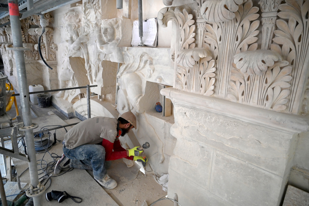 A restorer works on a sculpture on the upper part of the Royal Chapel of Versailles. — AFP pic