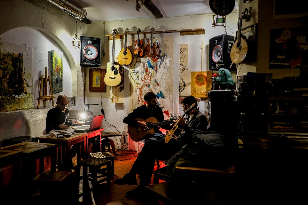 Two men play guitar during a jam session at the Tejo Bar in the Alfama neighbourhood in Lisbon May 16, 2019. — AFP pic