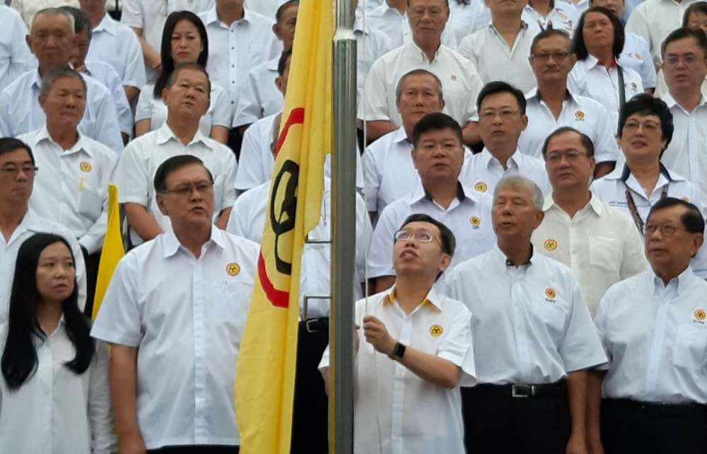 SUPP president Datuk Dr Sim Kui Hian raising the party's flag to mark the 60th anniversary of the party, June 4, 2019. ― Picture by Sulok Tawie