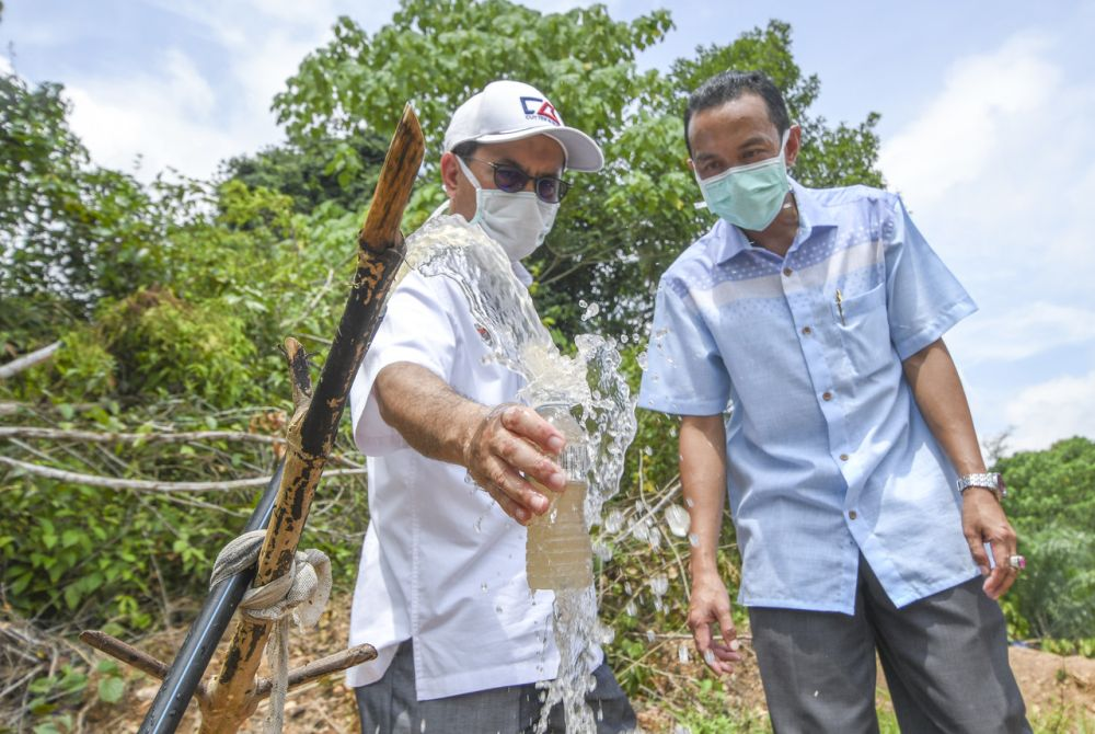 Deputy Minister of Water, Land Natural Resources Tengku Zulpuri Shah Raja Puji (left) collects water samples at Kampung Kuala Koh, Gua Musang June 9, 2019. — Bernama pic