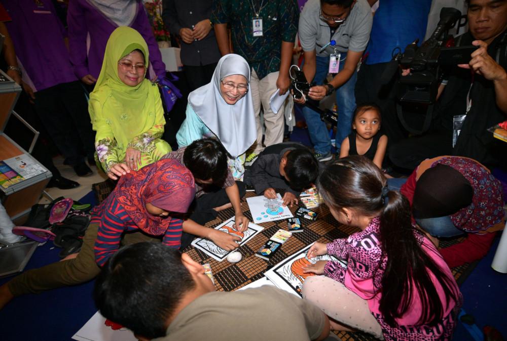 Deputy Prime Minister Datuk Seri Dr Wan Azizah Wan Ismail talks to children after officiating at the state-level 'Santuni Rakyat' programme at Mydin Petra Jaya, Sarawak, June 29, 2019. — Bernama pic