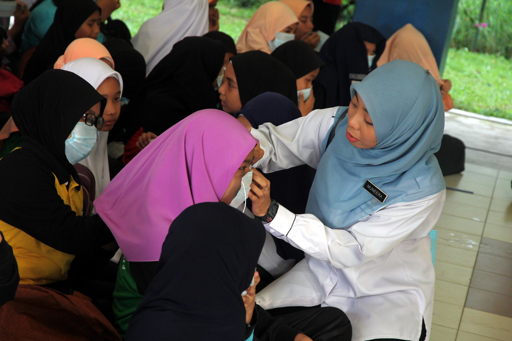 A teacher from SK Pasir Gudang 4 helps a student put on a face mask in Pasir Gudang, Johor June 30, 2019. — Bernama pic