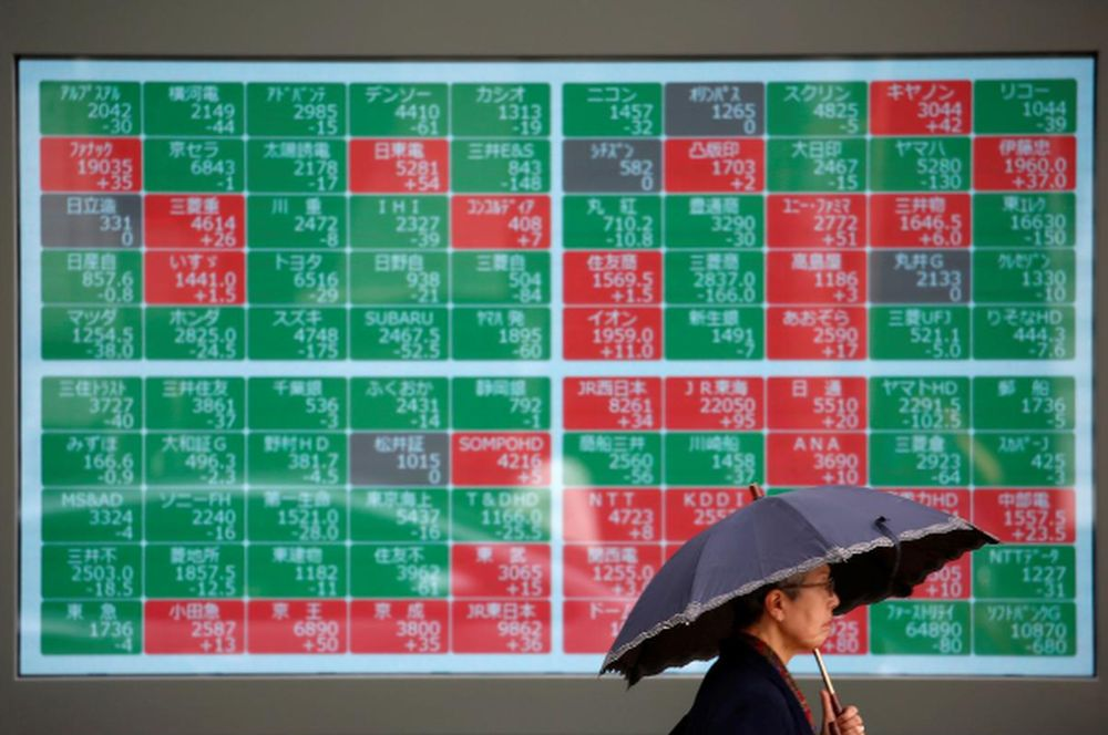 A passerby walks past in front of a stock quotation board outside a brokerage in Tokyo, Japan, May 10, 2019. — Reuters pic