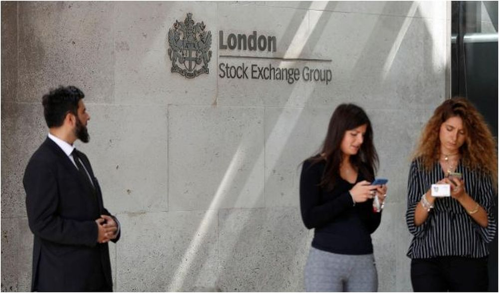 People check their mobile phones outside the entrance of the London Stock Exchange August 23, 2018. — Reuters pic
