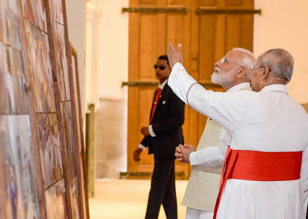 Archbishop of Colombo Cardinal Malcolm Ranjith (right) gestures next to Indian Prime Minister Narendra Modi during Modi's unscheduled stop at St. Anthony's Church in Colombo. — Handout / Sri Lankan Presidential Media Division/AFP pic