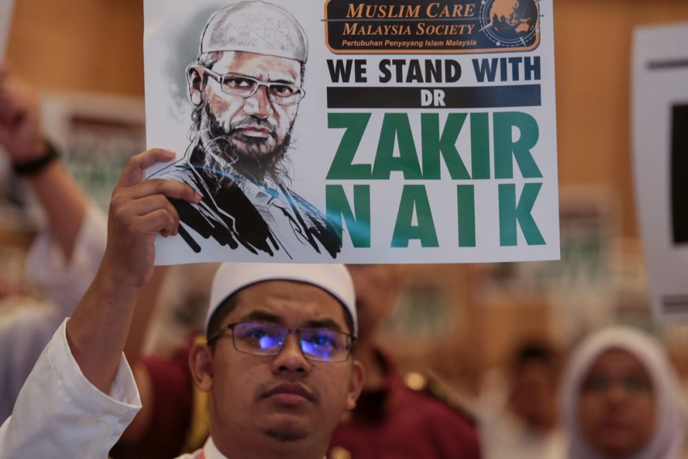 A PAS member holds up a placard to show his support for Dr Zakir Naik during Muktamar 2019 in Gambang, Pahang June 19, 2019. — Picture by Ahmad Zamzahuri
