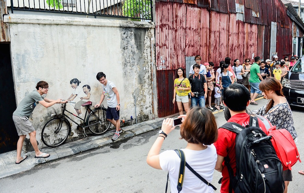 Tourists line up to take photos with the famous Little Children on a Bicycle mural by Ernest Zacharevic at Lorong Armenian in Georgetown. — Picture by Azrol Ali