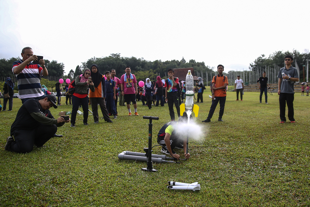 A student from SK Putrajaya Presint 18(1) launching a bottle rocket into the sky during the Venus Fun Run at Taman Wetlands, Putrajaya. — Picture by Yusof Mat Isa.