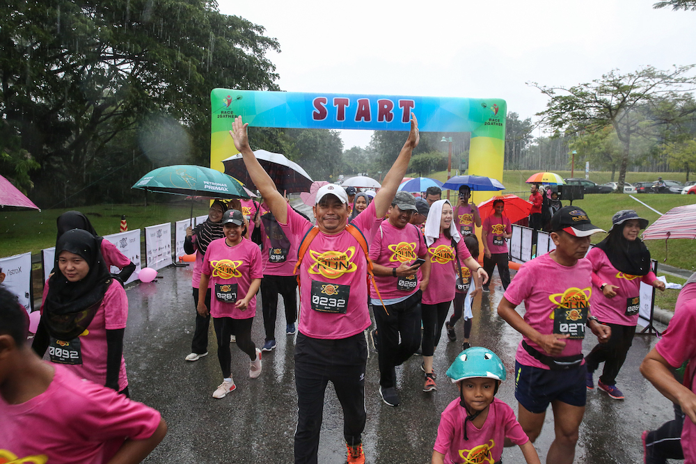 Contestants of the Venus Fun Run not letting a little rain get in their way as they race to complete the five-kilometre run. — Picture by Yusof Mat Isa.