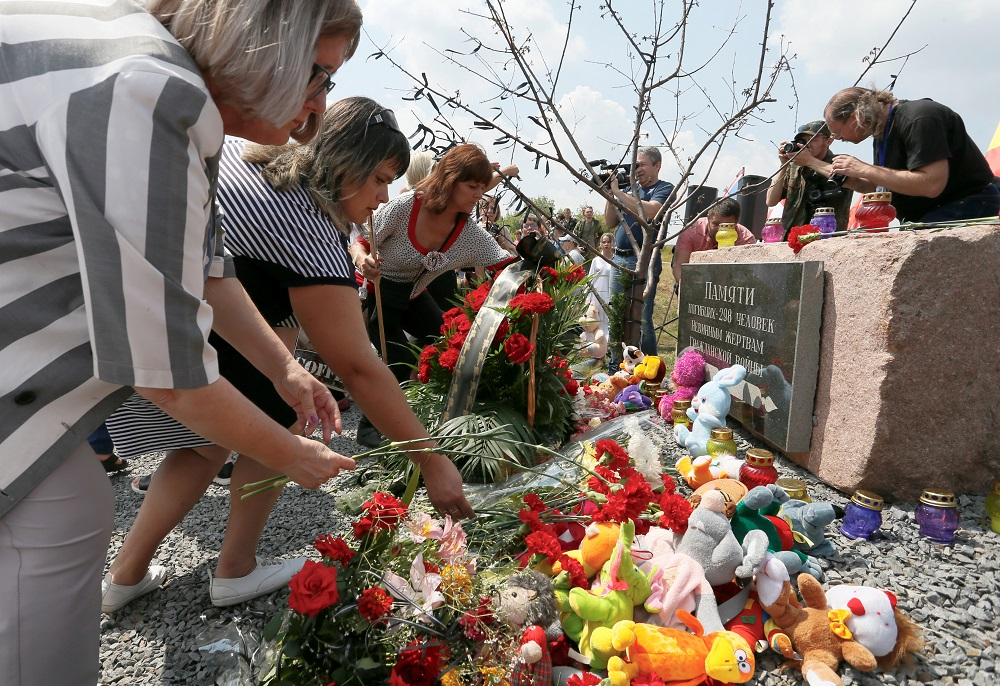 People place flowers and toys at a memorial to victims of the Malaysia Airlines Flight MH17 plane crash during a ceremony marking the fifth anniversary of the accident near the village of Hrabove in Donetsk Region, Ukraine July 17, 2019. — Reuters pic