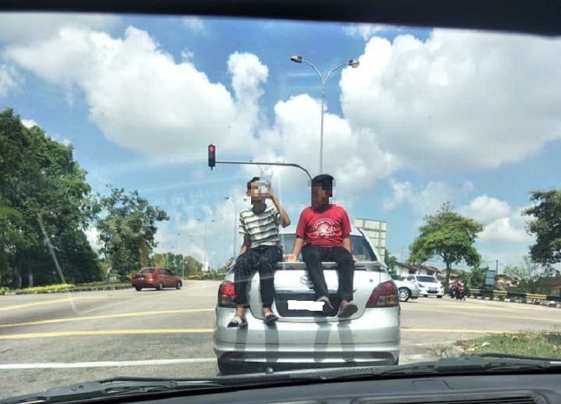 A screen capture of the video showing the two boys seated at the back of a moving silver Toyota Vios. — Picture courtesy of Armada JB WhatsApp group