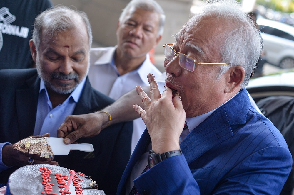 Datuk Seri Najib Razak is greeted with cheers and a chocolate cake for his 66th birthday at the lobby of the Kuala Lumpur Court Complex July 23, 2019. — Picture by Mukhriz Hazim