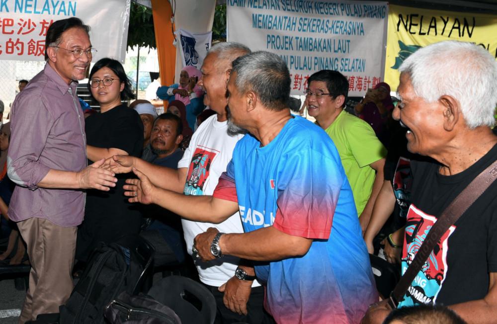 PKR president Datuk Seri Anwar Ibrahim shakes hands with fishermen from Sungai Batu Teluk Kumbar at a meeting with residents and fishermen at Permatang Damar Laut in Penang July 13, 2019. — Bernama pic