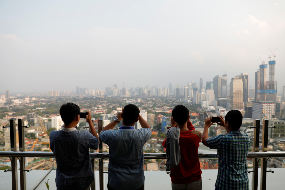 Boys use their smartphones as smog covers the capital city of Jakarta, Indonesia, July 4, 2019. — Reuters pic