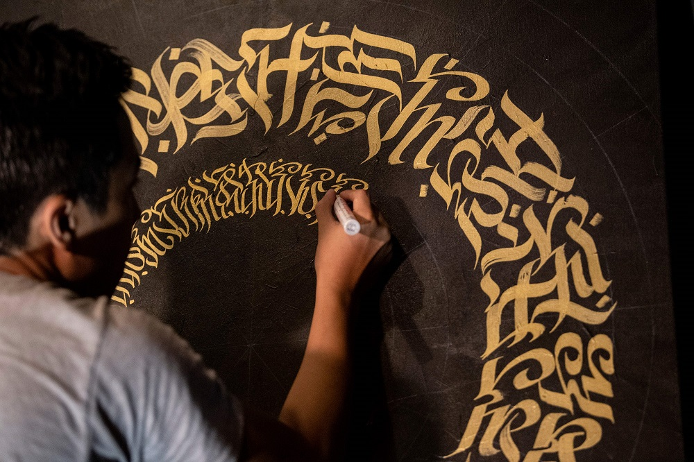 This photo taken on June 22, 2019 shows artist Taipan Lucero doing calligraphy using the indigenous script known as Baybayin, used before Spanish colonisation in 1521, at an event in Manila. — AFP pic