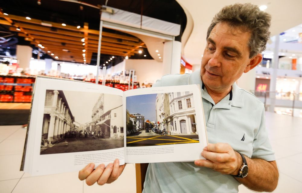 Marcus Langdon holds up a copy of 'Penang, Then And Now', during an interview with Malay Mail in George Town July 2, 2019. ― Picture by Sayuti Zainudin
