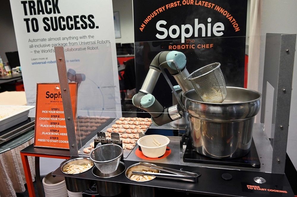 This picture taken on July 26, 2019 shows Sophie the robotic chef preparing to make laksa, a local dish of rice noodles served in a curry sauce, in Singapore. — AFP pic