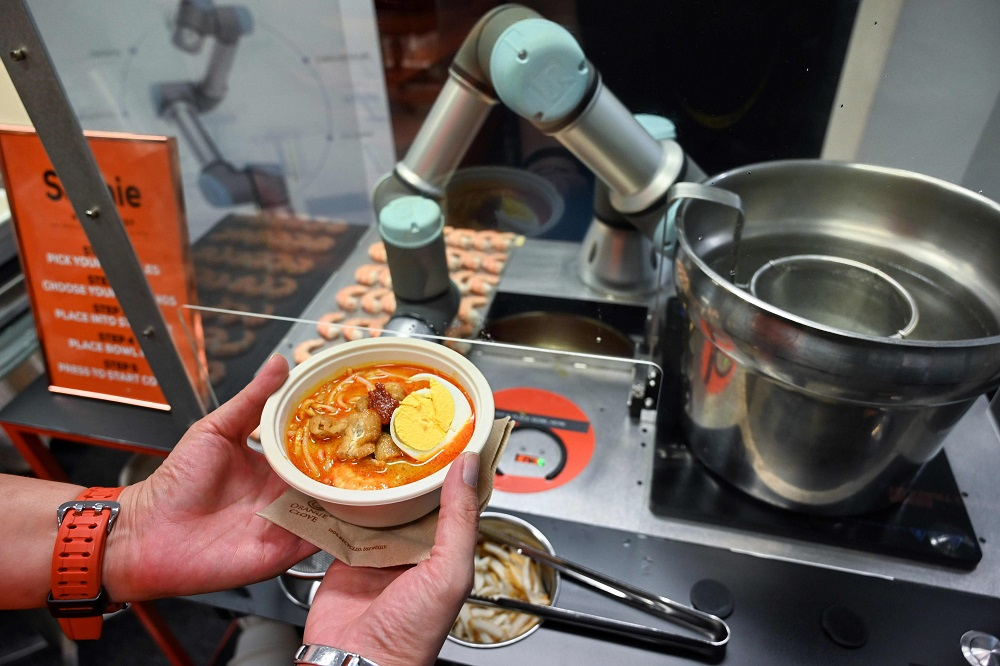 This picture taken on July 26, 2019 shows a person holding a bowl of laksa, a local dish of rice noodles served in a curry sauce, after it was prepared by Sophie the robotic chef in Singapore. — AFP pic