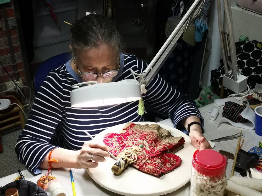 Conservator Kim Siebert restores an antique puppet at the Taiyuan Asian Puppet Theatre Museum in Taipei, Taiwan.
