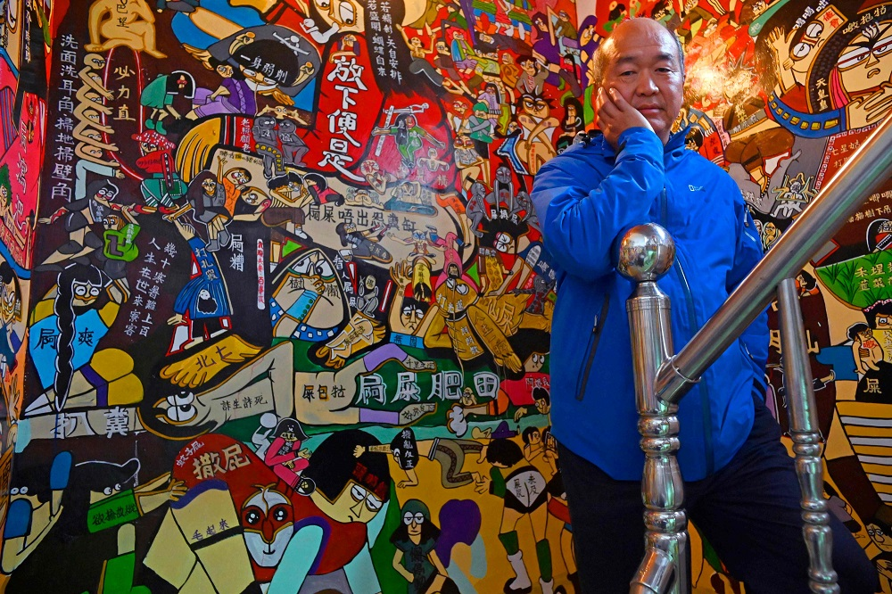 This picture taken on March 30, 2019 shows Hakka graffiti artist Wu Tsun-hsien posing for photos at his home in the Taiwanese village of Ruan Chiao. — AFP pic