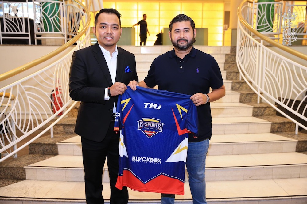 Johor Crown Prince Tunku Ismail Sultan Ibrahim receiving a Esports Malaysia Association (ESM) jersey, emblazoned with his initials TMJ, from the association's general secretary Hisham Darus. — Picture courtesy of HRH Crown Prince of Johor Facebook