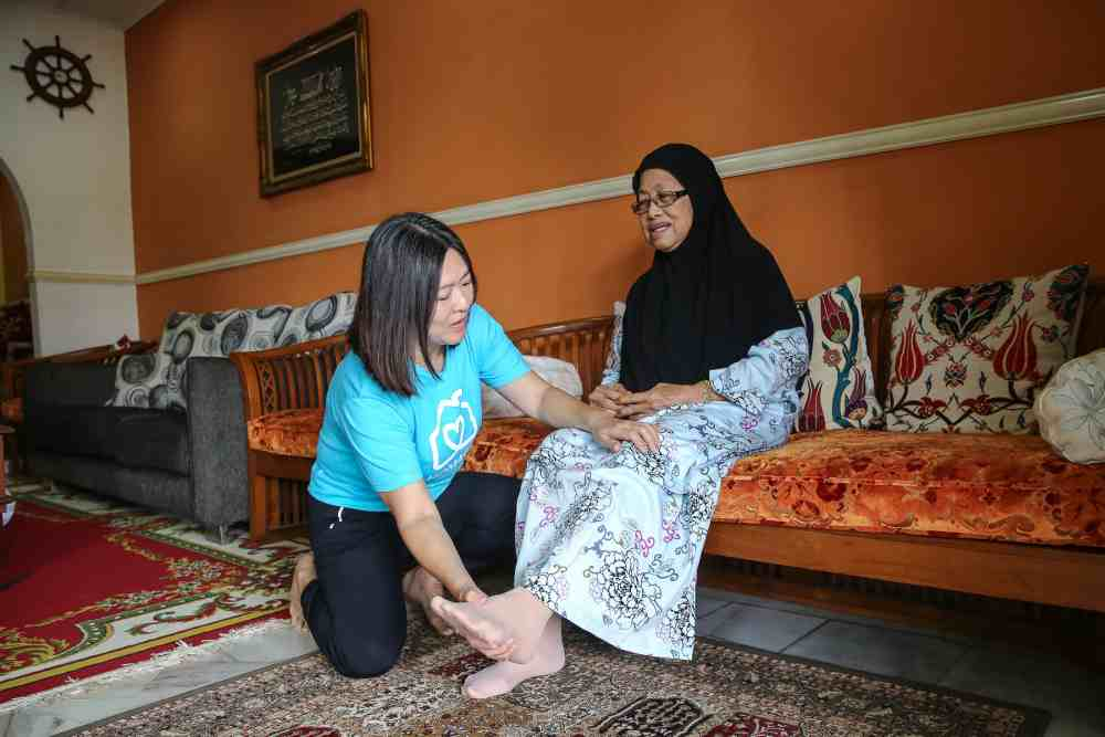 Jane Yap (in blue) looks after a care recipient in her home. — Picture by Yusof Mat Isa