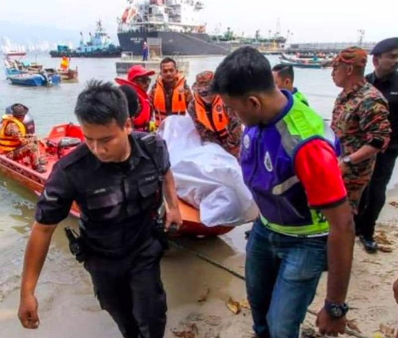 Rescue personnel carry the victim's body out of the water. ― Picture via Facebook/Penang Kini