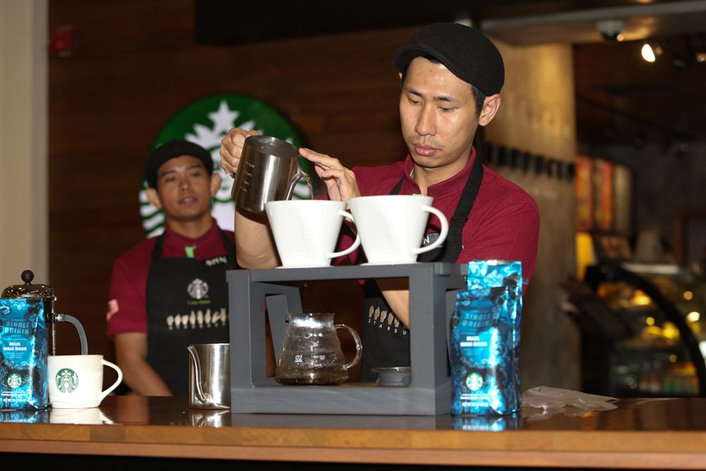"""Yap Yee Lin demonstrating the proper way to brew coffee using the """"Pour Over"""" brewing method."""