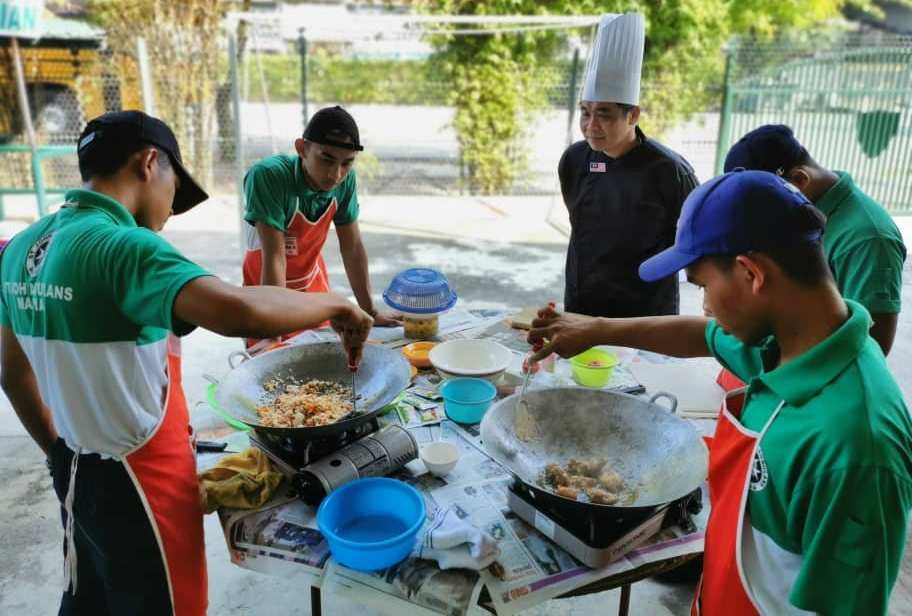 Chef Alan Wong checking the dishes cooked by participants of  the 40th Cooking and Flag Signalling Competition. — Picture courtesy of St John Ambulance Malaysia, Perak chapter