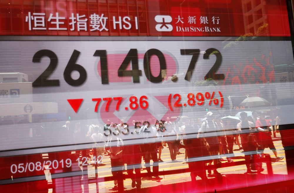 The reflections of pedestrians are seen on a screen displaying the Hang Seng Stock index in Hong Kong August 5, 2019. — Reuters pic