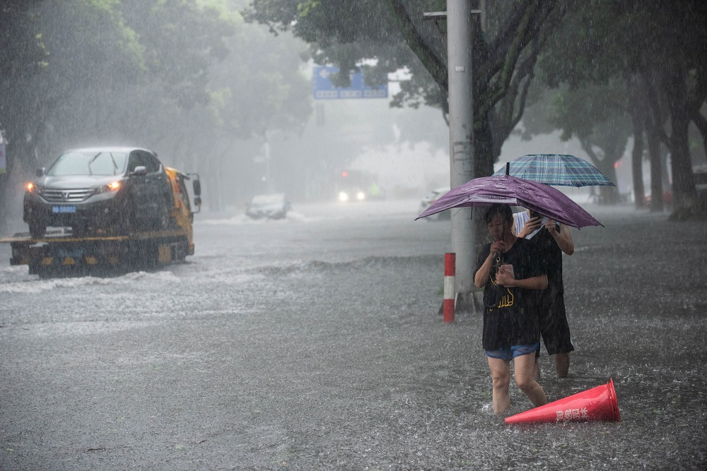 People holding umbrellas wade through floodwaters amid heavy rainfall on a street after super typhoon Lekima made landfall in Ningbo, Zhejiang province, China August 10, 2019. — Picture by Stringer via Reuters
