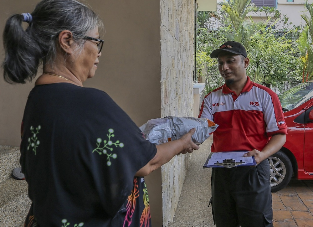 Yuzali delivers a parcel to a customer in Sri Hartamas, Kuala Lumpur. — Picture by Firdaus Latif