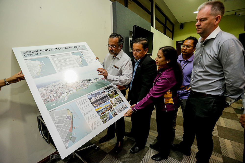 Jagdeeo Singh Deo and Penang Port Commission chairman Jeffrey Chew (2nd left) look at an artist's impression of the East Seafront Project at Swettenham Pier in George Town August 1, 2019. — Picture by Sayuti Zainudin