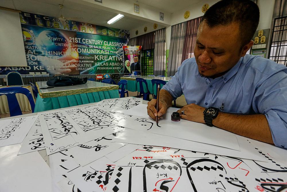 A man creates khat art in Balik Pulau, Penang August 6, 2019. — Picture by Sayuti Zainudin