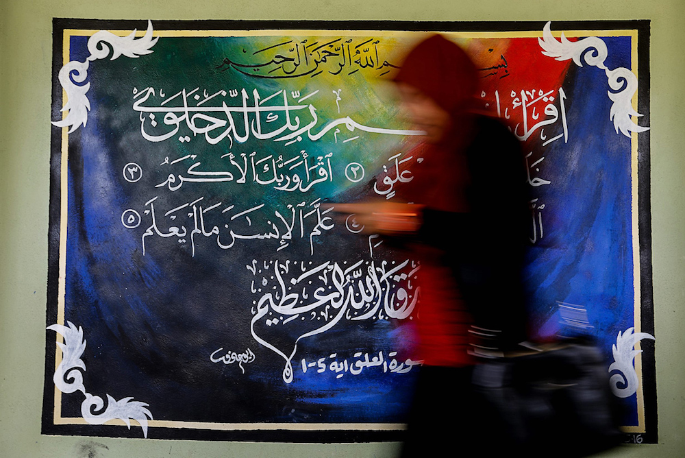 A woman walks past a piece of khat calligraphy in Balik Pulau, Penang August 6, 2019. — Picture by Sayuti Zainudin