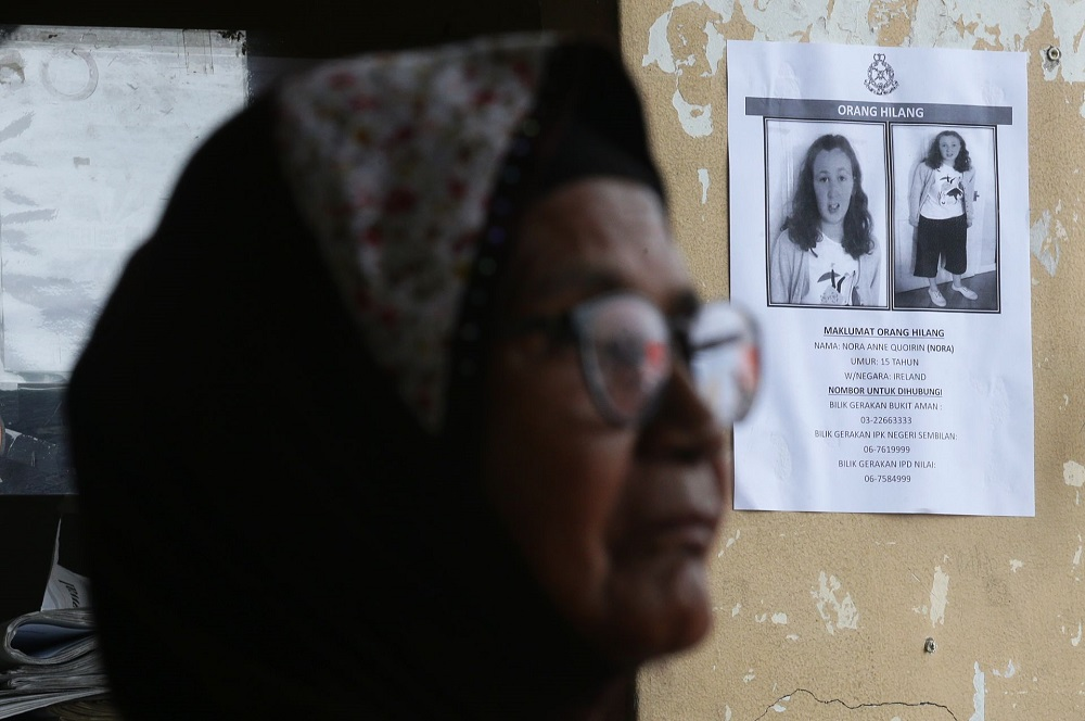 A woman walks past a poster featuring missing Irish teenager Nora Anne Quoirin in Seremban August 10, 2019. — Picture by Ahmad Zamzahuri